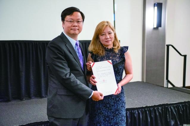 經濟文化辦事處處長黃鈞耀,代表僑委會頒發感謝獎狀給會長楊于萱