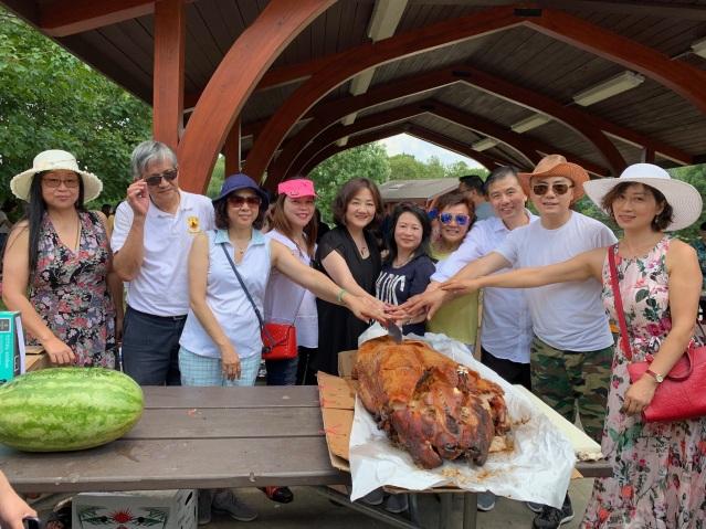 照片七:邊志春副總領事(中)與香港會成員共切燒豬