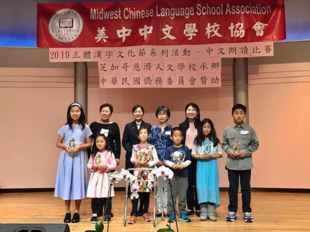固德中文學校劉玉娥校長(後排左二),頒發優勝獎座給「語言藝術組」的小朋友們